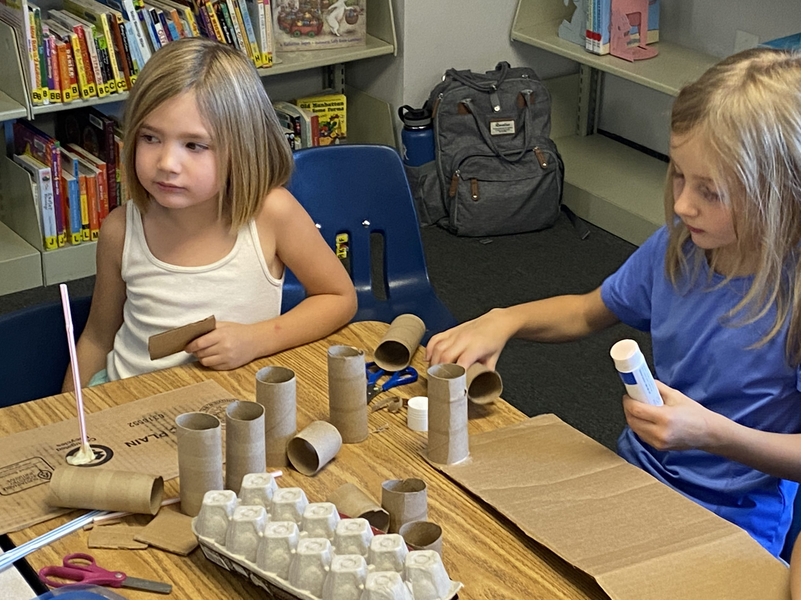 two girls making crafts with toilet paper tubes and cardboard